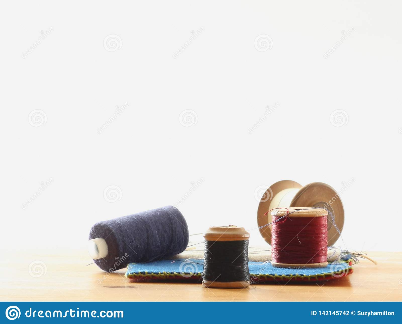 Cuatro carretes del algodón cerca para arriba en una tabla con un caso de la costura en un fondo blanco