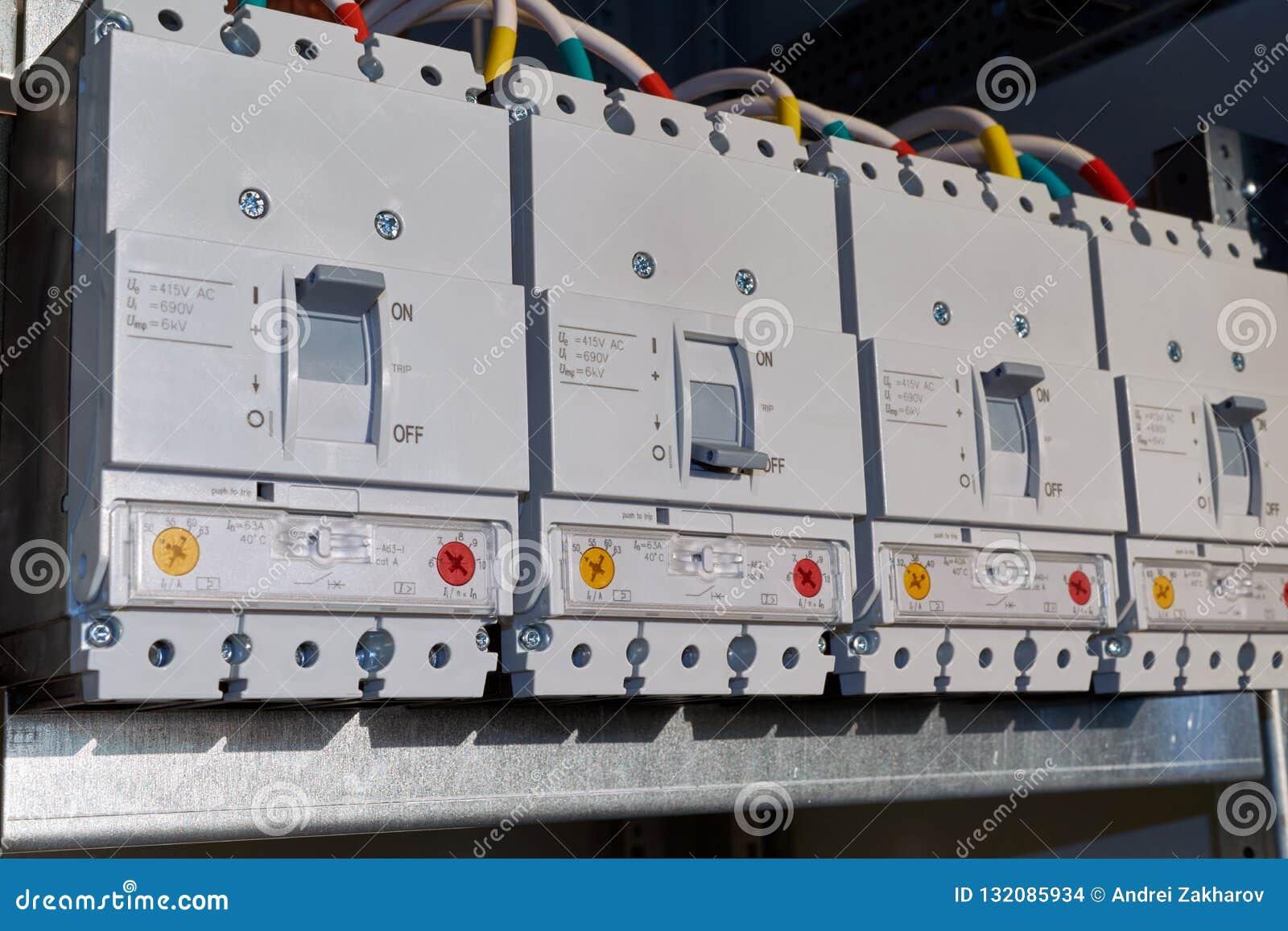 Cuatro disyuntores de poder se fijan en el gabinete eléctrico en línea