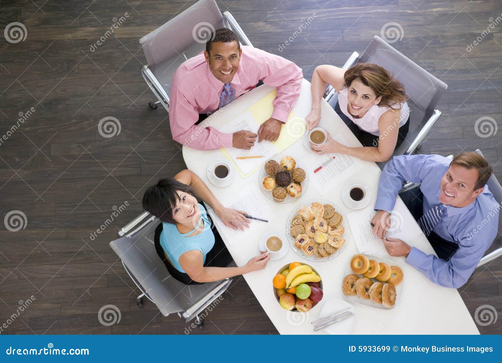 Cuatro empresarios que comen en el vector de la sala de reunión