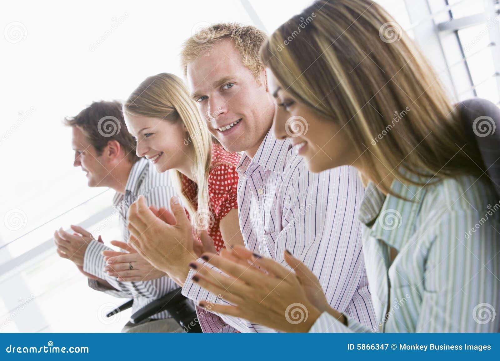 Cuatro hombres de negocios que aplauden dentro la sonrisa