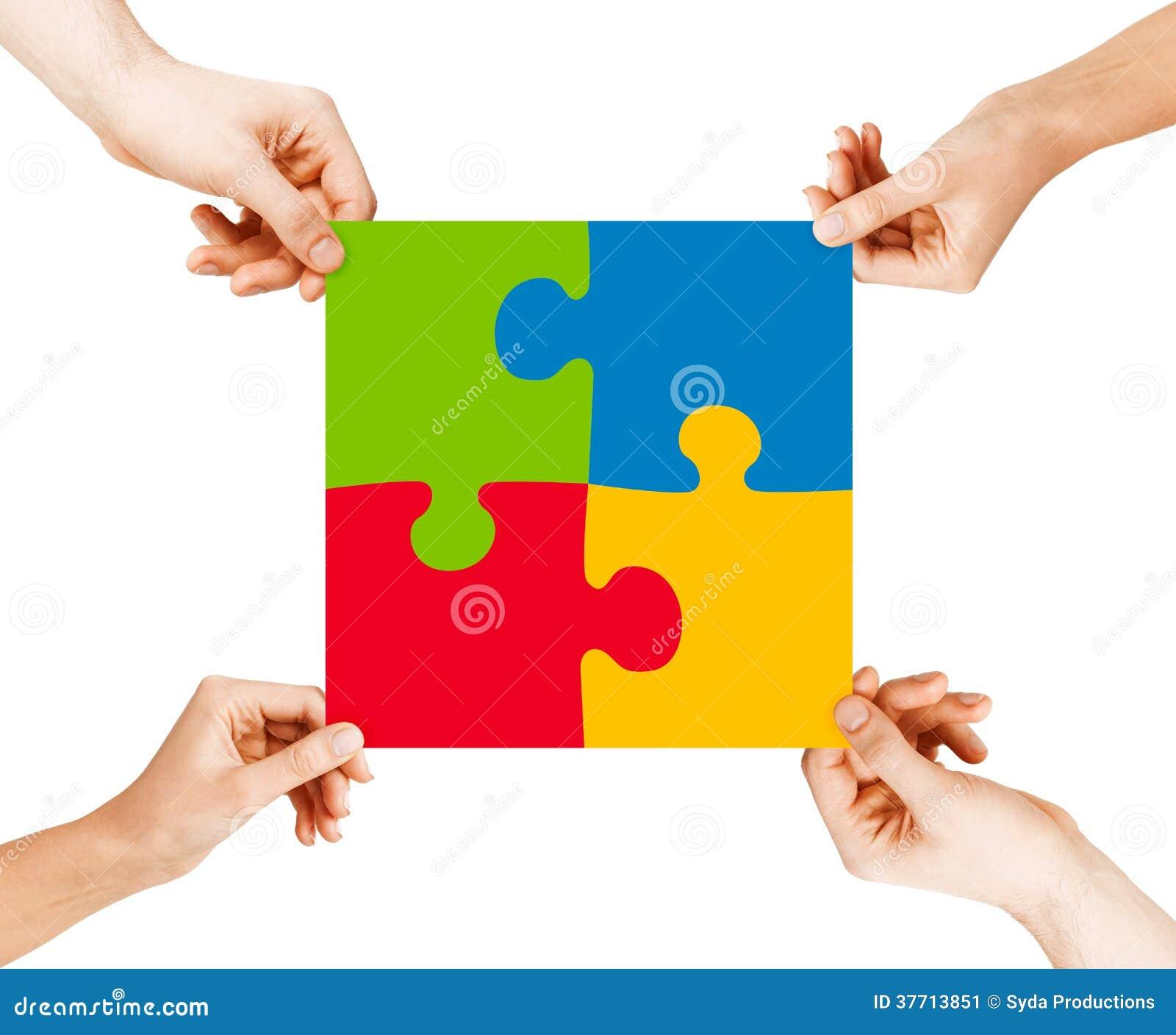 Cuatro manos que conectan pedazos del rompecabezas