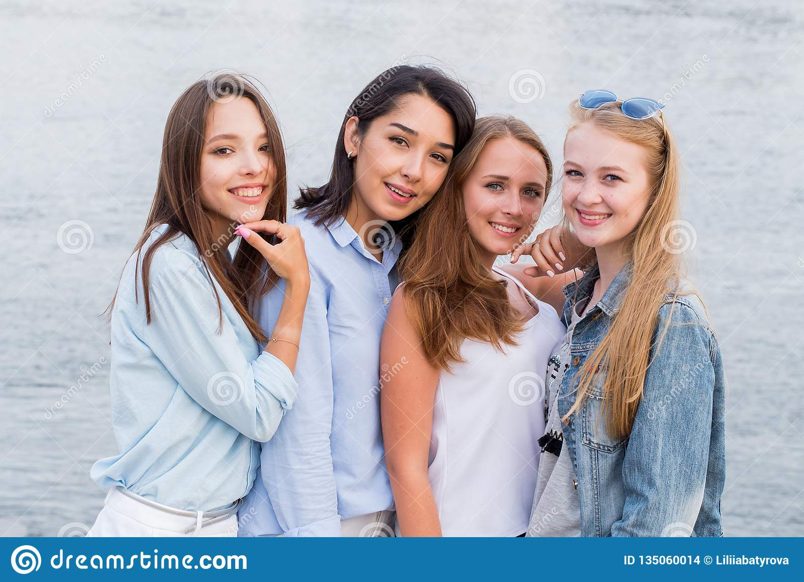 Cuatro mejores novias que miran la cámara junto gente, forma de vida, amistad, concepto de la vocación Muchacha alegre joven del