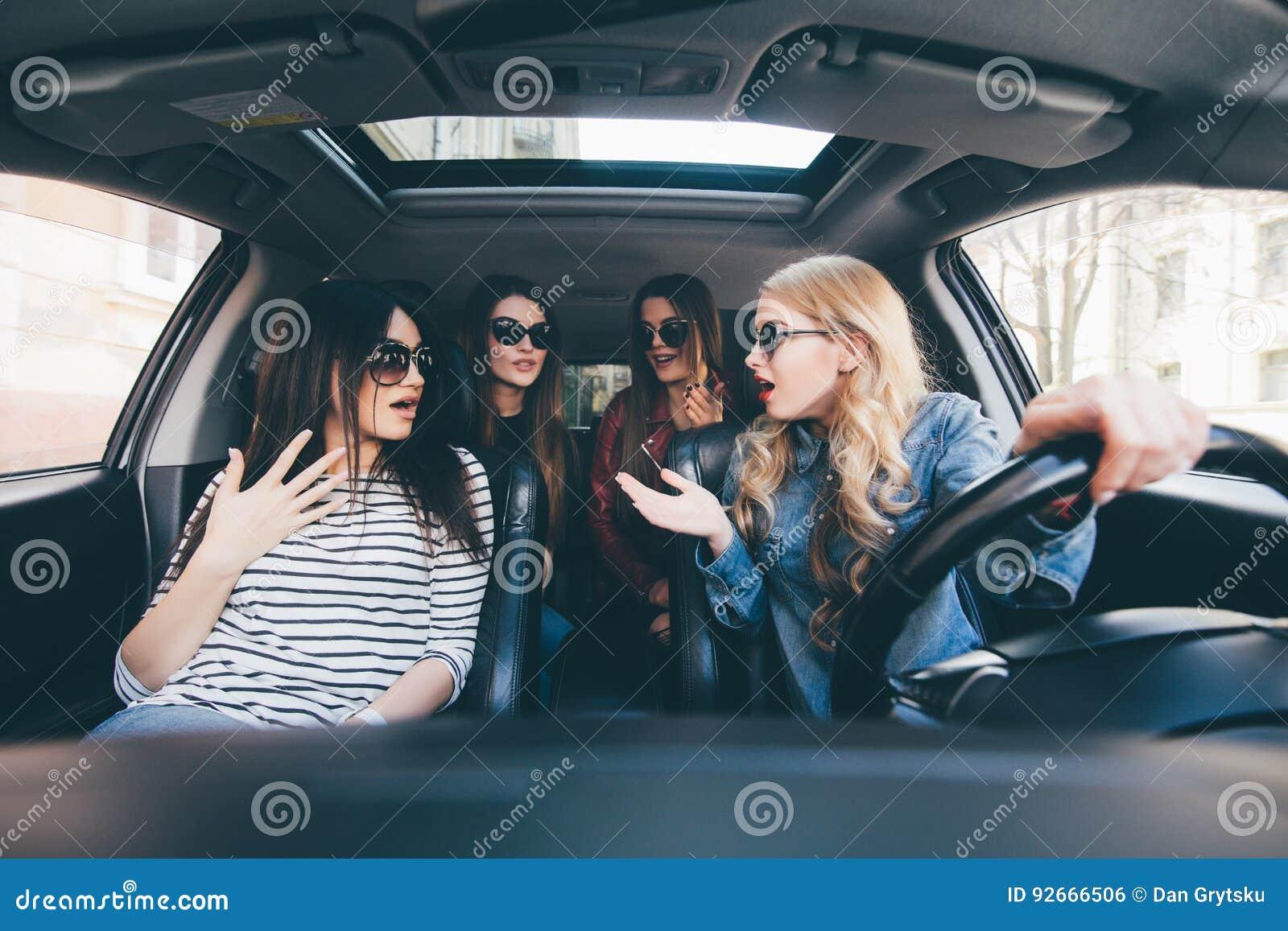 Cuatro mujeres alegres jovenes hermosas que miran uno a con sonrisa mientras que se sienta en coche