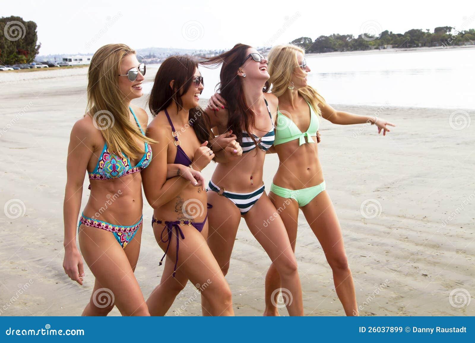 Cuatro mujeres jovenes hermosas que gozan de la playa