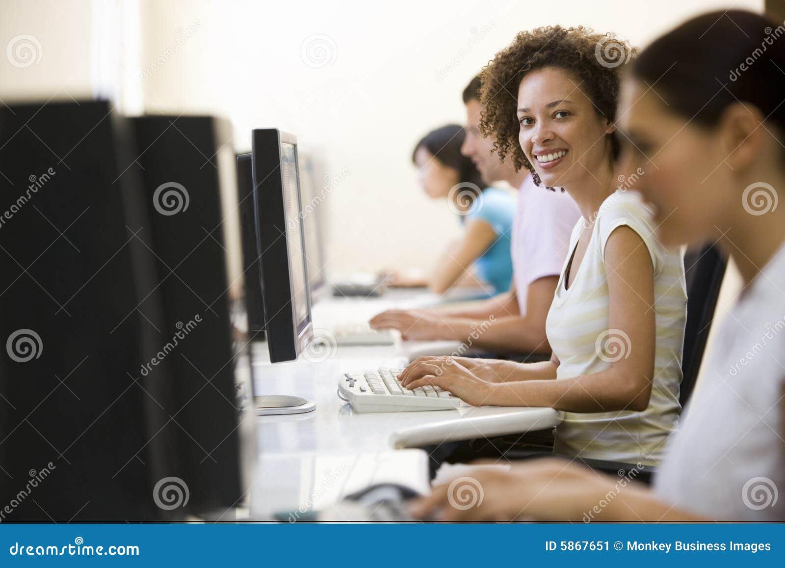 Cuatro personas en sala de ordenadores que pulsan y que for Hotel para cuatro personas