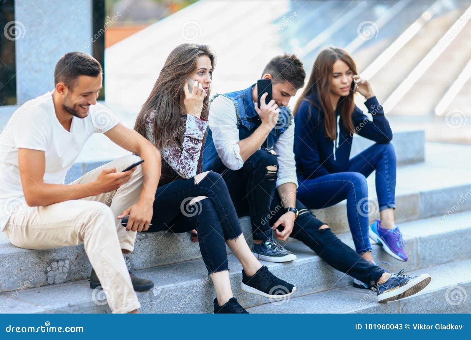 Cuatro personas jovenes que se sientan en las escaleras y que usan los teléfonos móviles