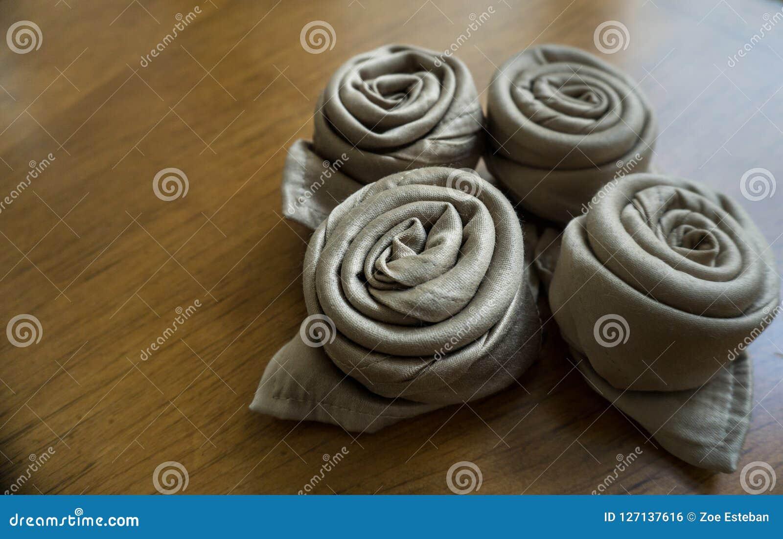 Cuatro rosas de oro de la papiroflexia de la servilleta sobre un fondo de madera listo para los eventos, las celebraciones de los