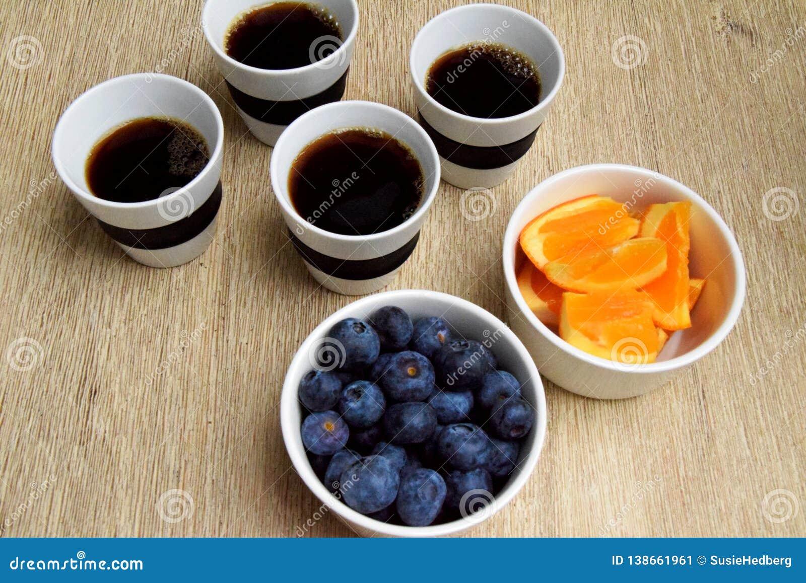 Cuatro tazas de café y de bocado sano de la fruta
