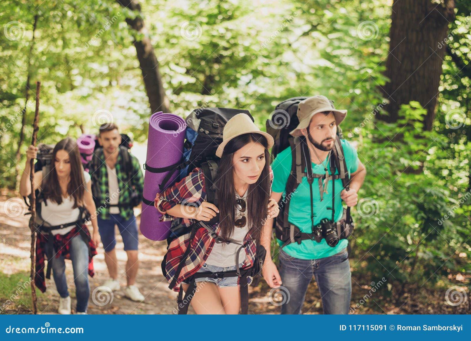 Cuatro turistas consiguieron perdidos en el bosque, intentando encontrar la manera, pareciendo serios y enfocados, todos que tení