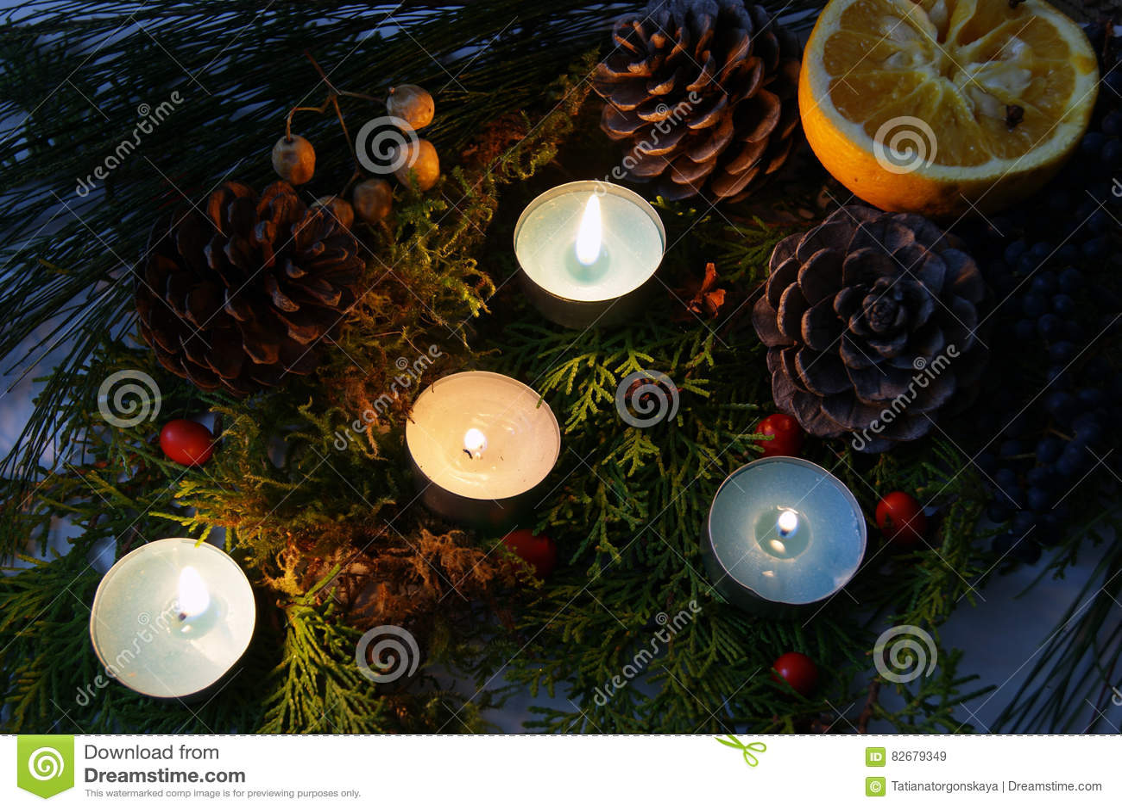Cuatro velas ardientes entre decoraciones de la Navidad