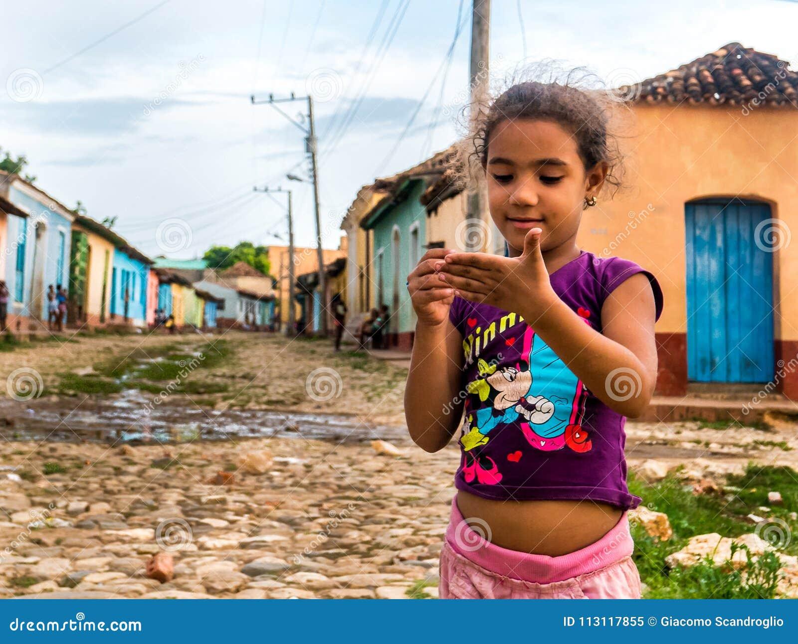 Cuba, Trinidad Em junho de 2016: caçoe a menina que joga com o lápis na rua, cercada por casas coloridas de Trinidad