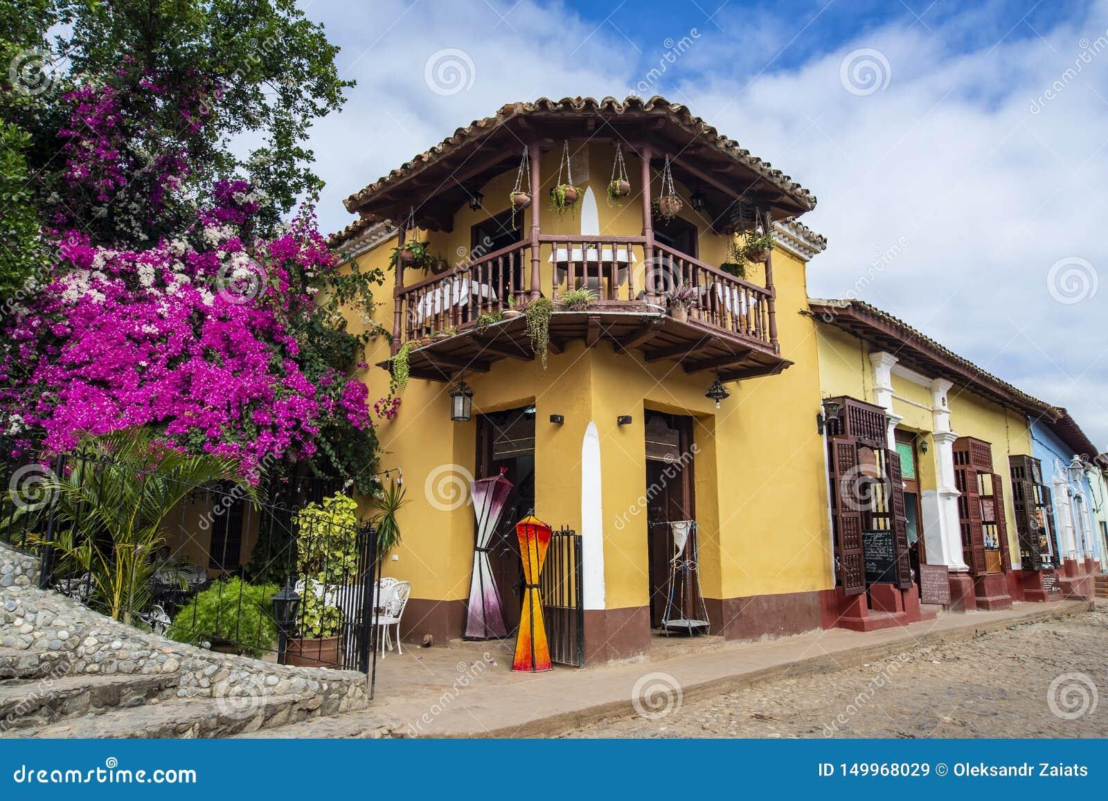 Cuba Trinidad Hoek van oud twee vloer de bouwrestaurant met violette en purpere bloemen Mooie hemel met wolken