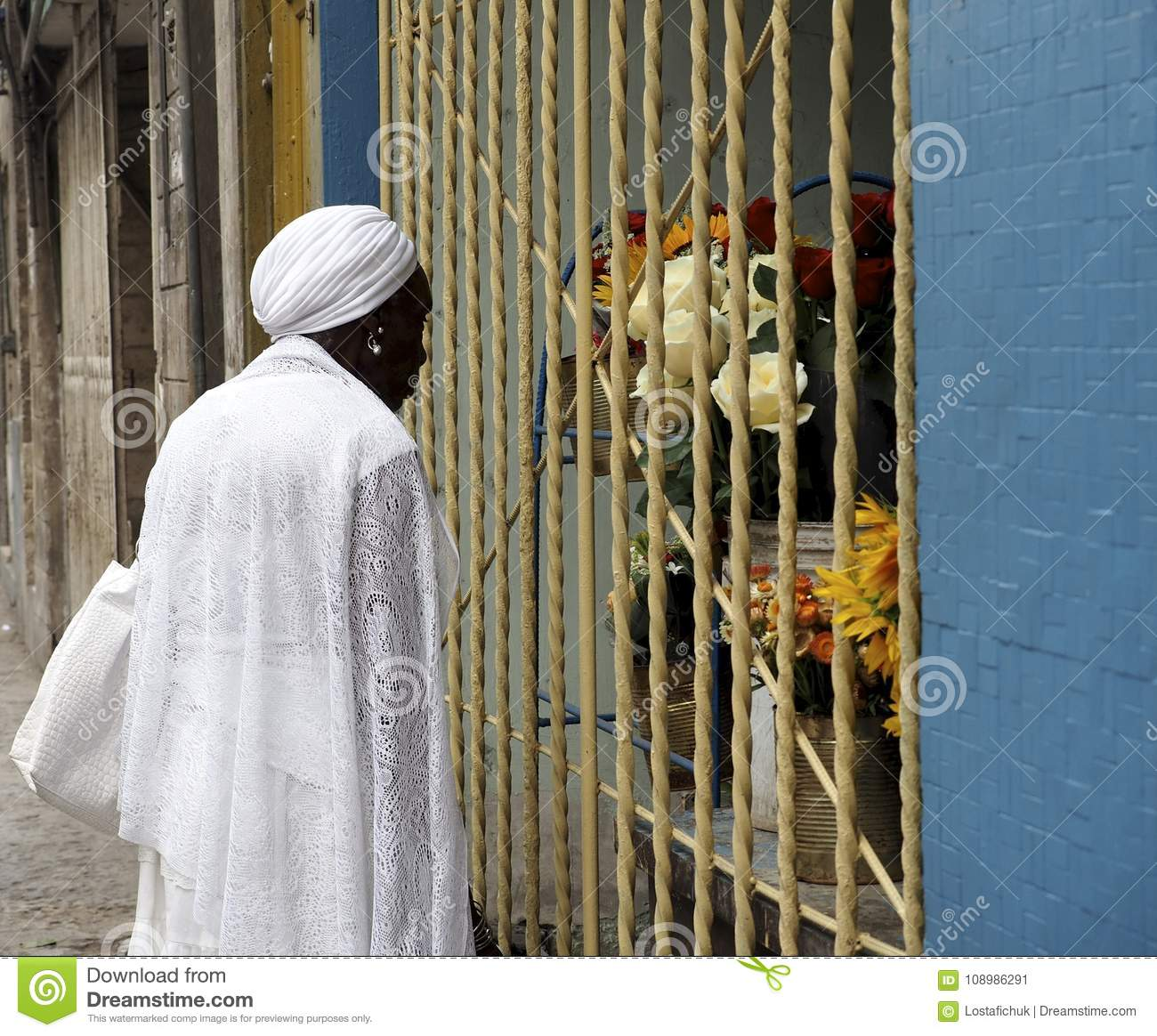 Cuban Lady Dressed In White Looking At Flowers