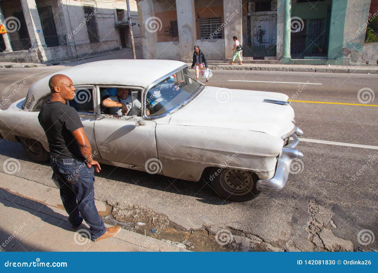 Cubano desconhecido perto de um táxi retro nas ruas de uma área perigosa de Serrra