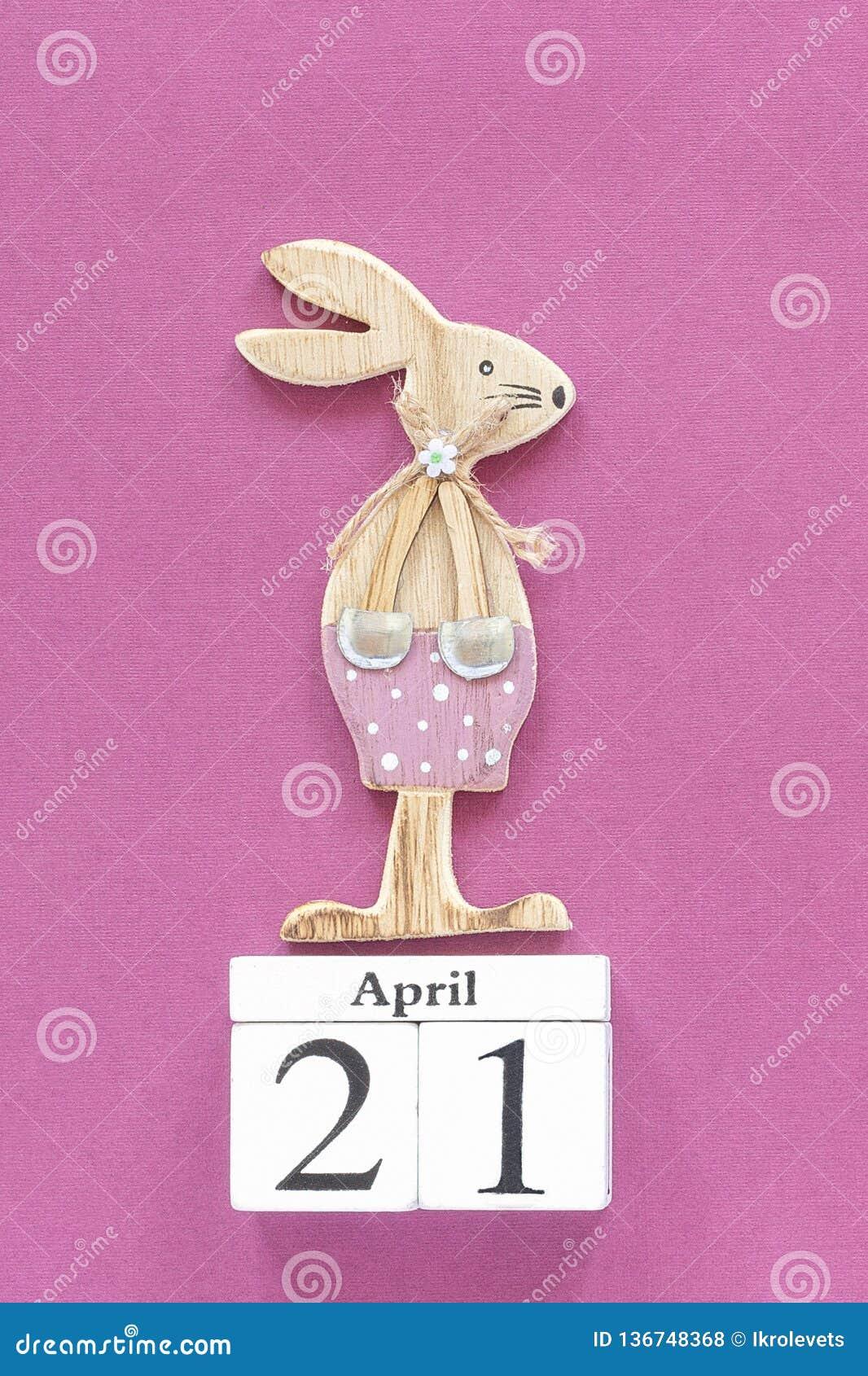 Cubes calendrier 21 avril et lapin de Pâques en bois sur le fond de papier pourpre Calibre catholique de Pâques de concept pour m