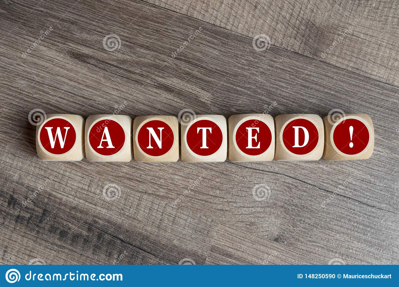 Cubes and dice with word wanted on wooden background