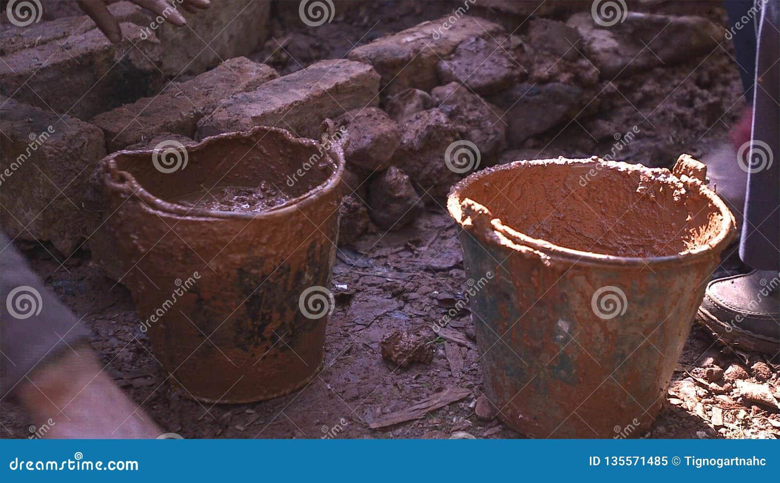 Cubeta suja com argila, solo na terra para a construção da casa da lama
