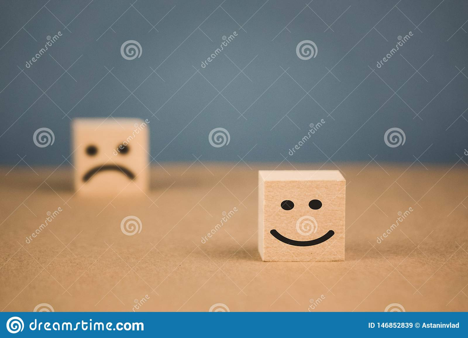 Cubi di legno con gli emoticon sorridenti e quello triste