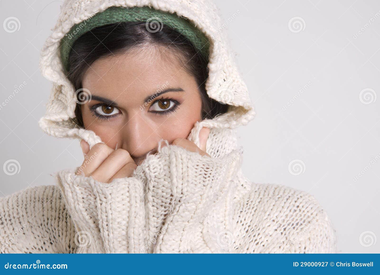 Cubierta atractiva de la mujer media su cara con el suéter