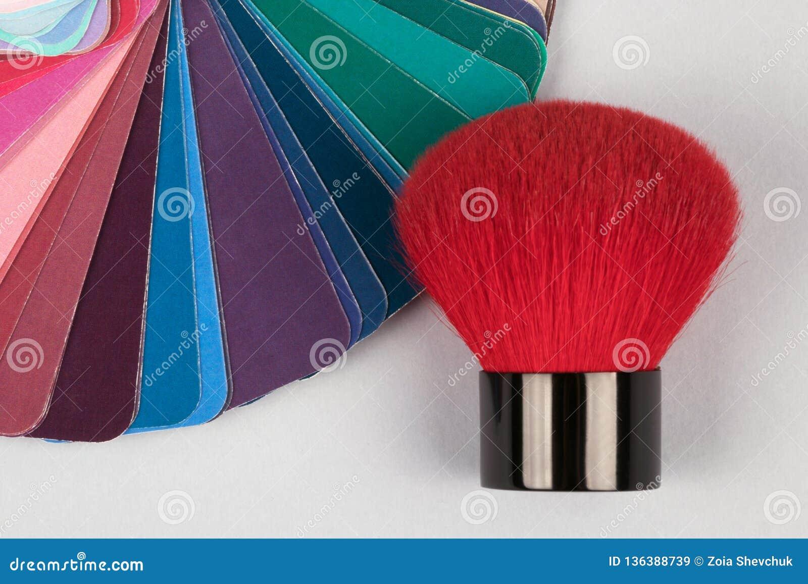 Cubierta de la fan del color con las muestras de diversas pinturas con el cepillo rojo para el maquillaje