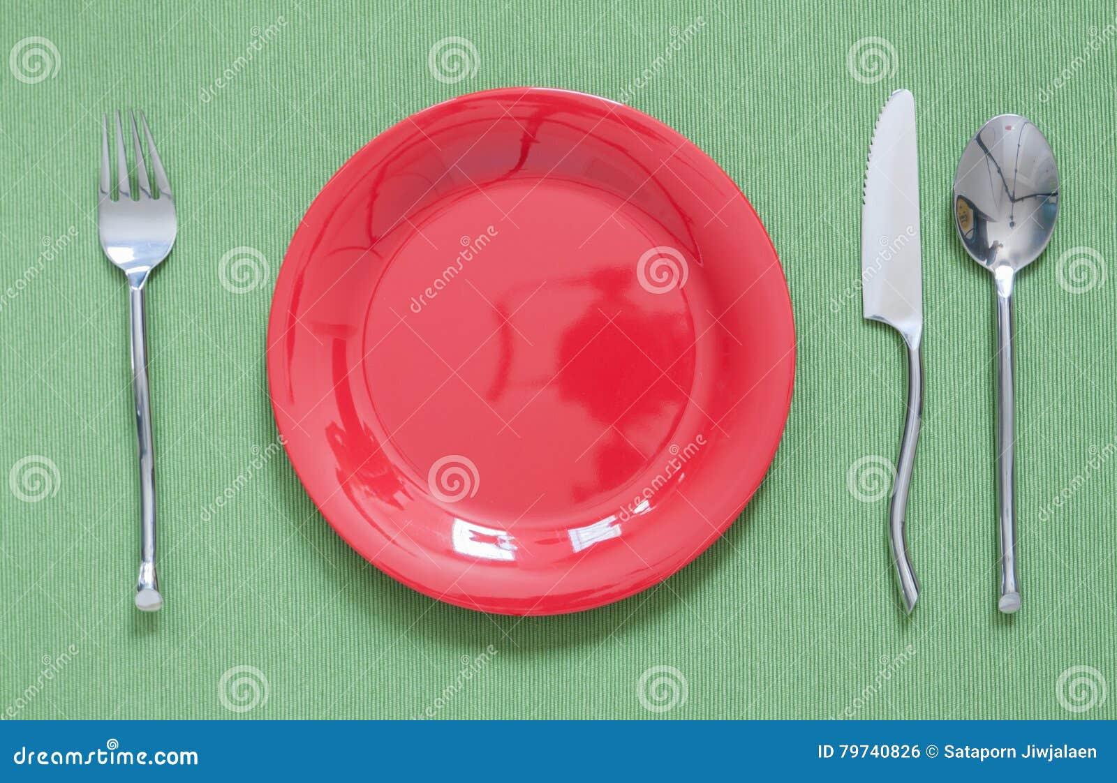 Cubierto de la cena una placa roja con la bifurcación de plata