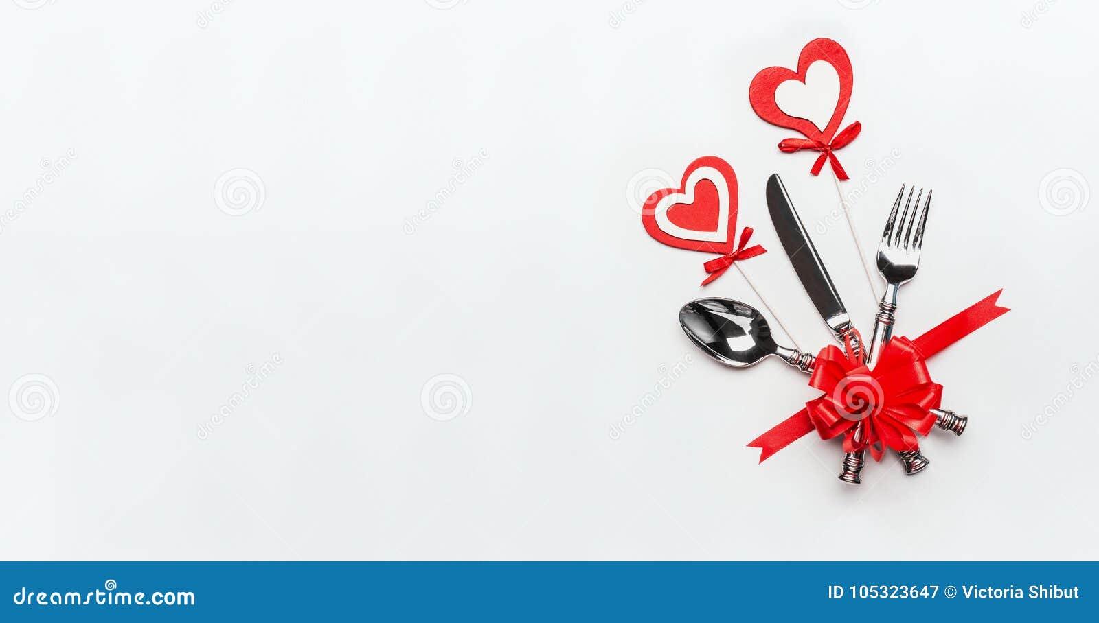 Cubierto festivo de la tabla con los cubiertos y la cinta roja y corazones en el fondo blanco, bandera