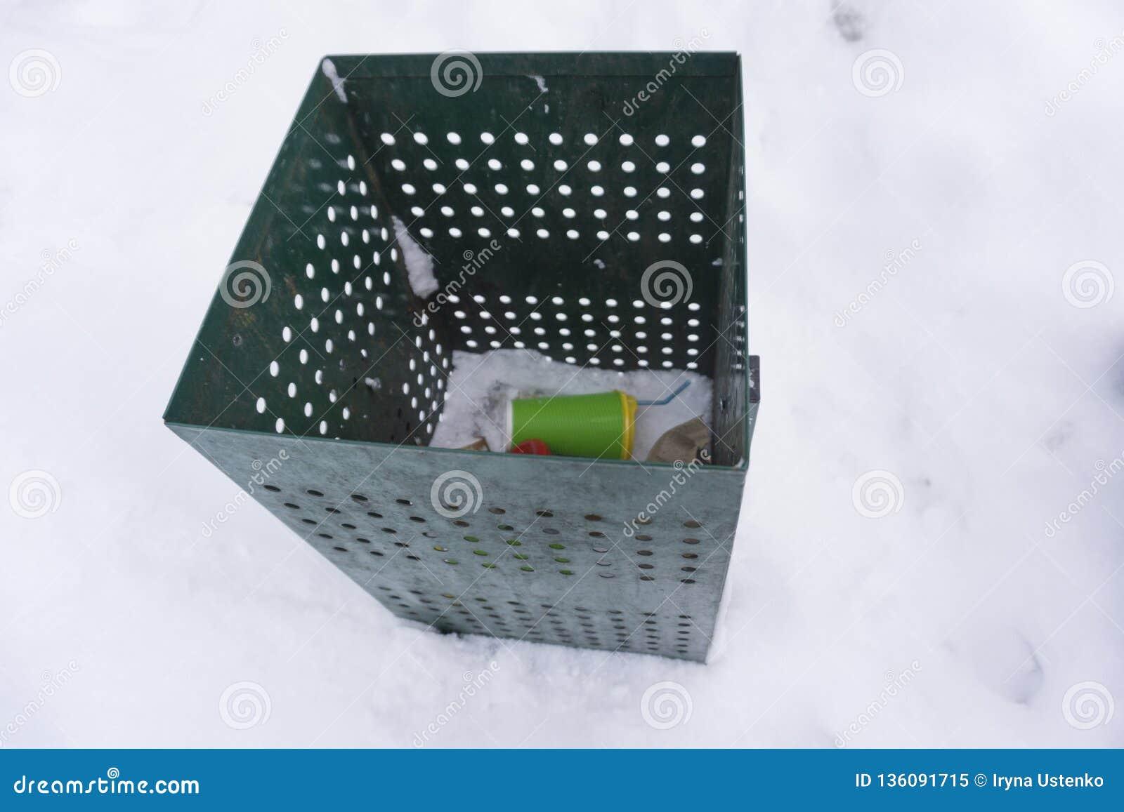Cubo de la basura verde encima con las tazas de café
