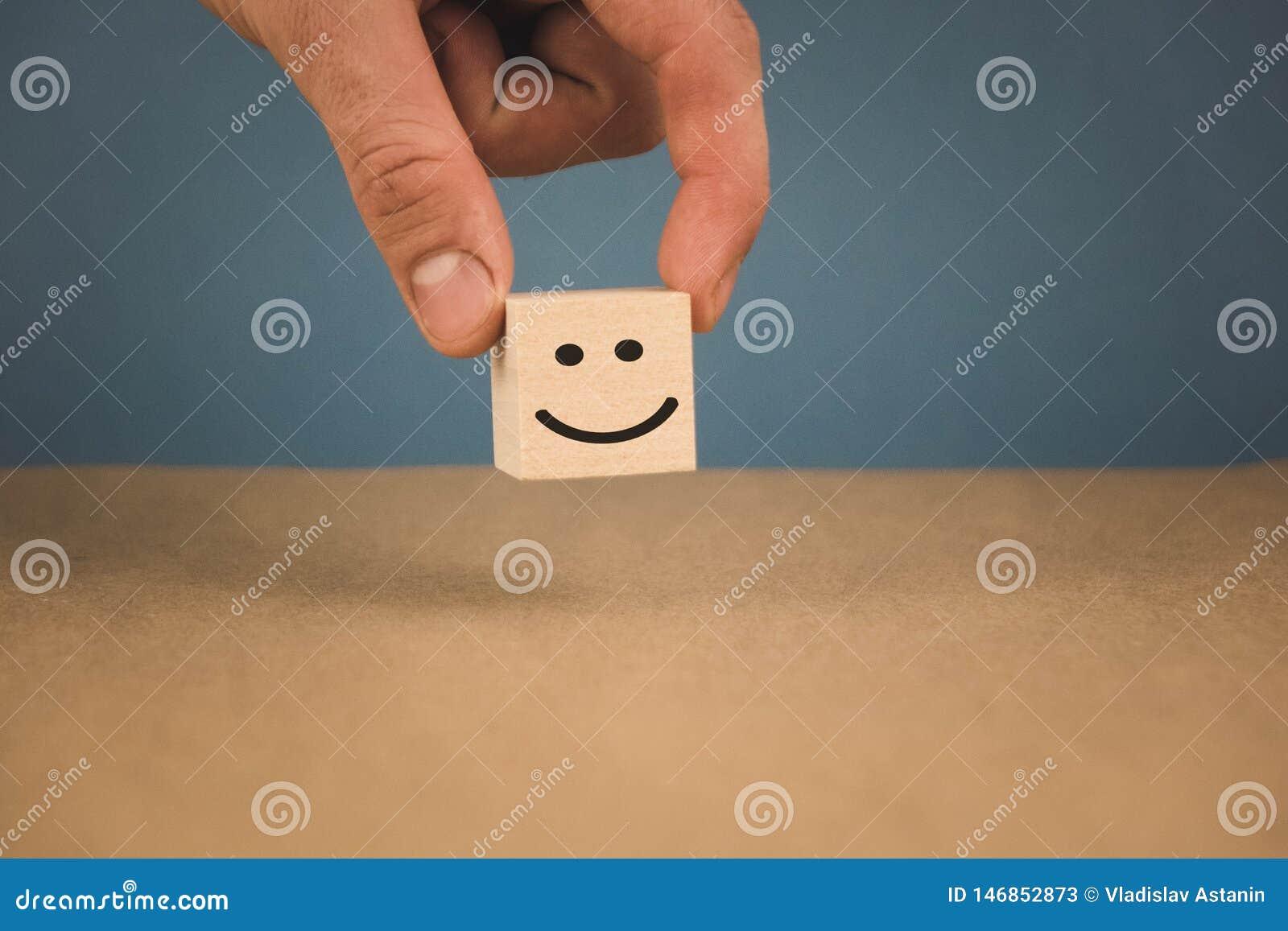 Cubo de madera y la imagen de un smiley sonriente que es la mano de los in person
