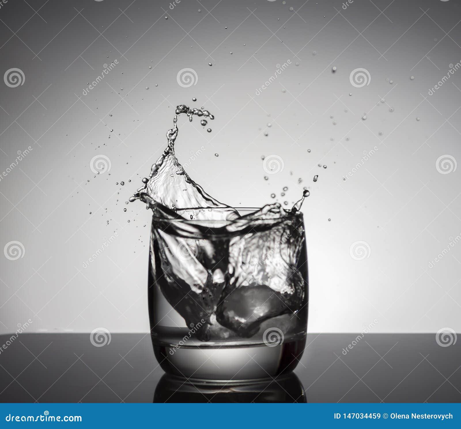 Cubos de gelo que espirram no vidro da ?gua