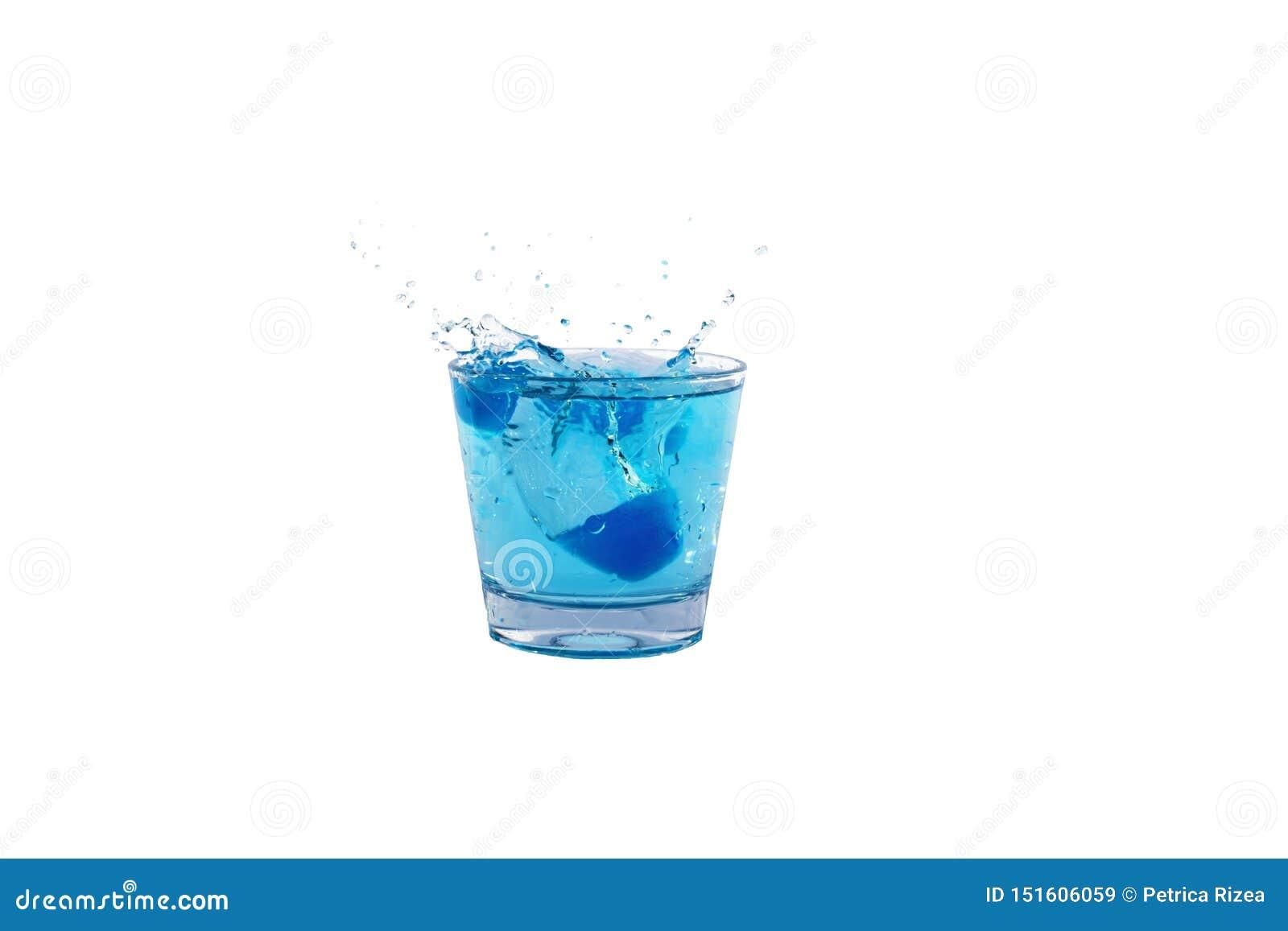 Cubos de hielo azules que salpican en el vaso de agua