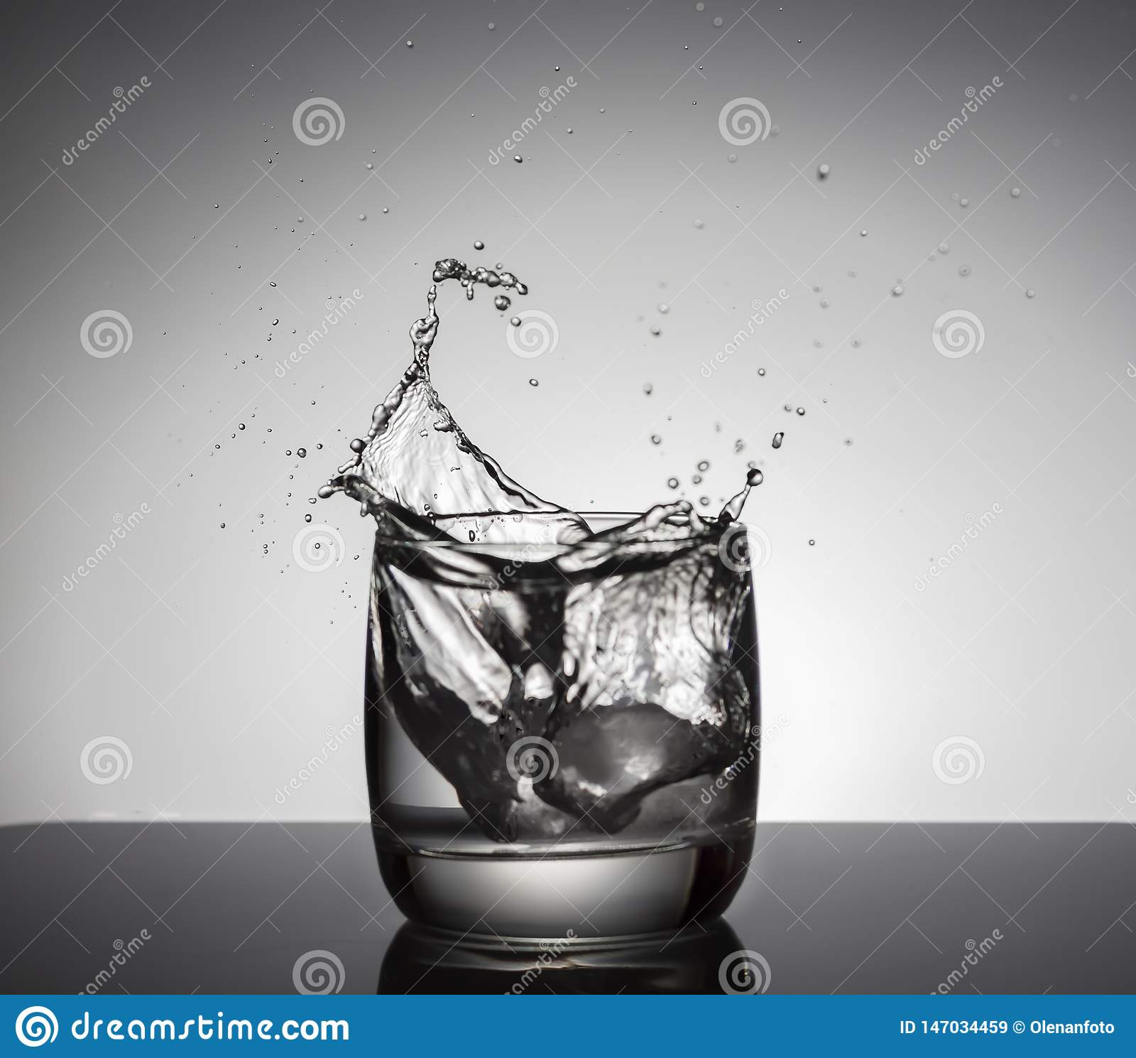 Cubos de hielo que salpican en el vidrio de agua