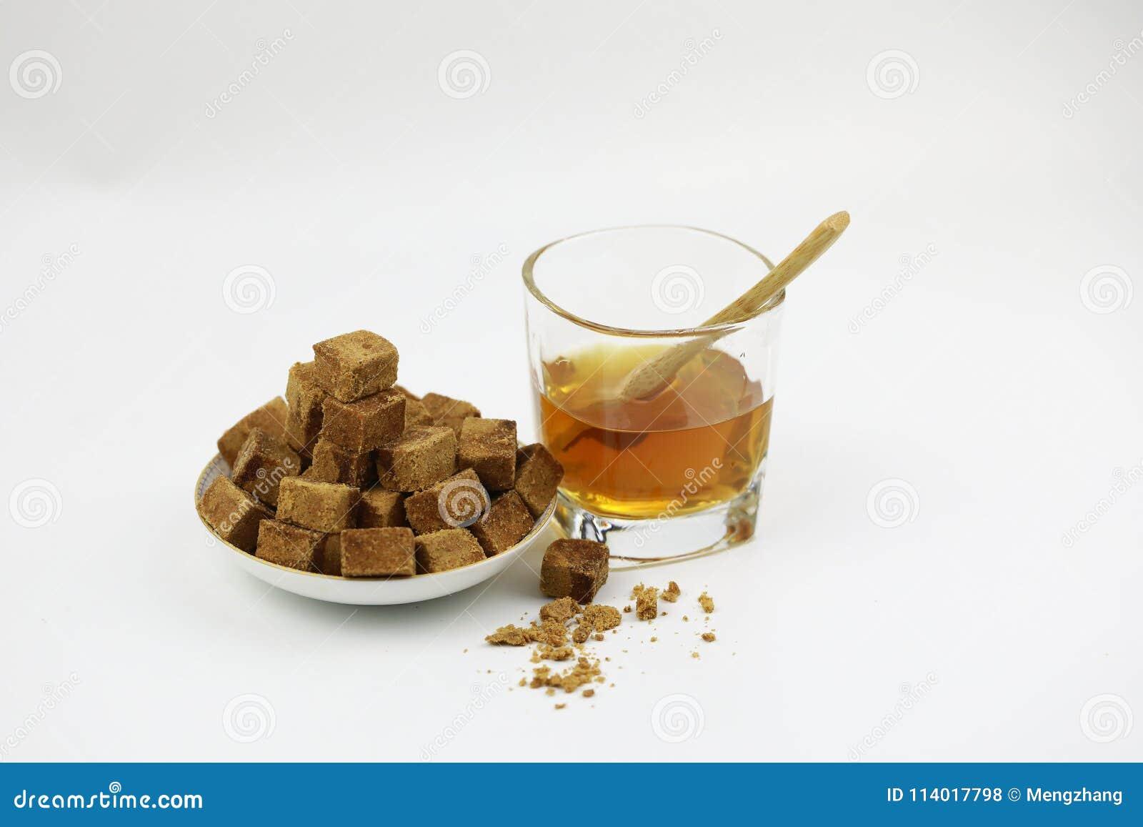Cubos del azúcar en la placa y la taza de cristal con agua