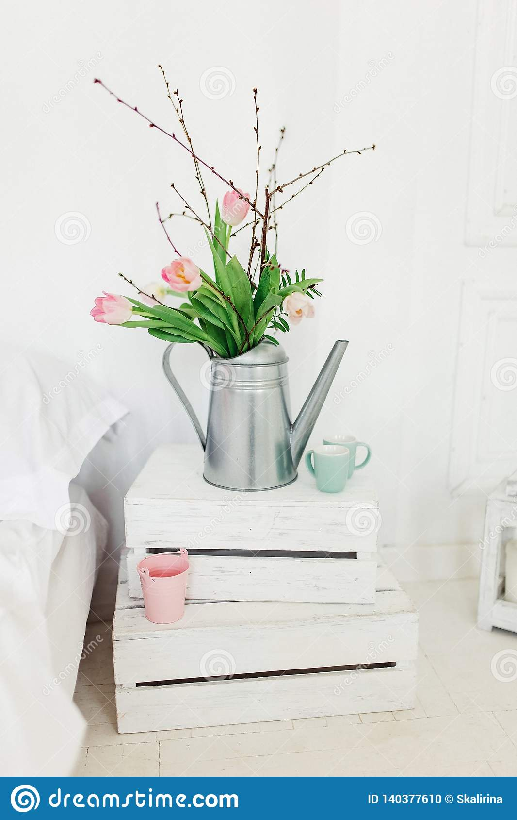 Cubra con cinc la regadera con los tulipanes rosados sobre el fondo blanco en dormitorio