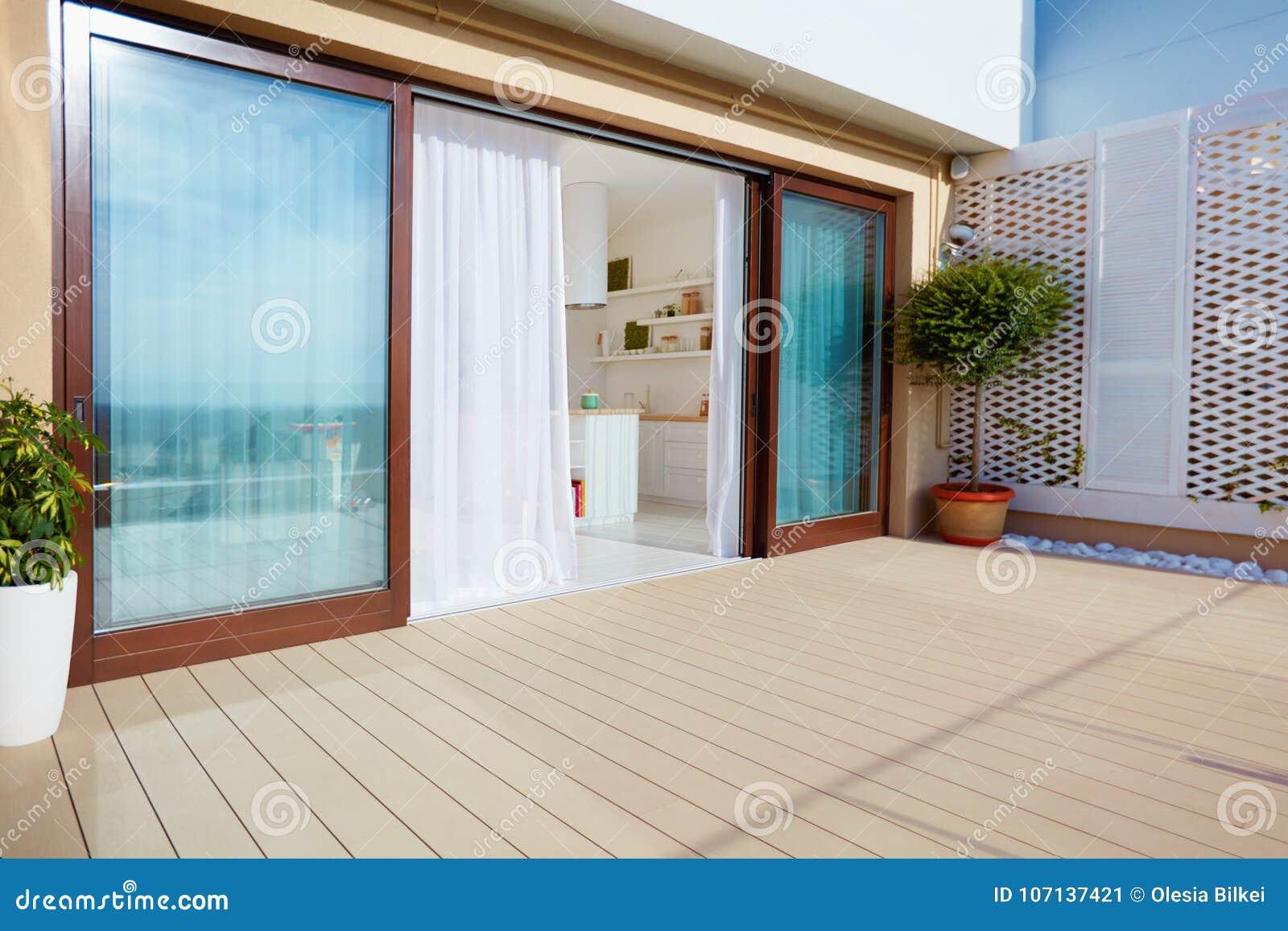 Cubra el patio superior con la cocina del espacio abierto, las puertas deslizantes y decking en piso superior