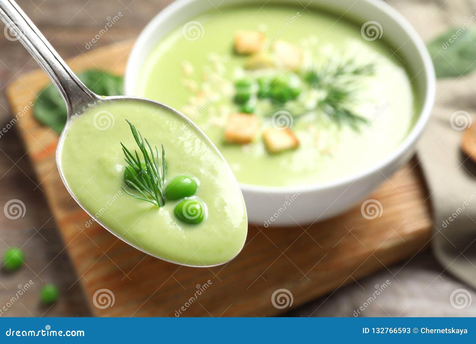 Cucchiaio con la minestra della disintossicazione di verdura fresca fatta dei piselli su fondo vago