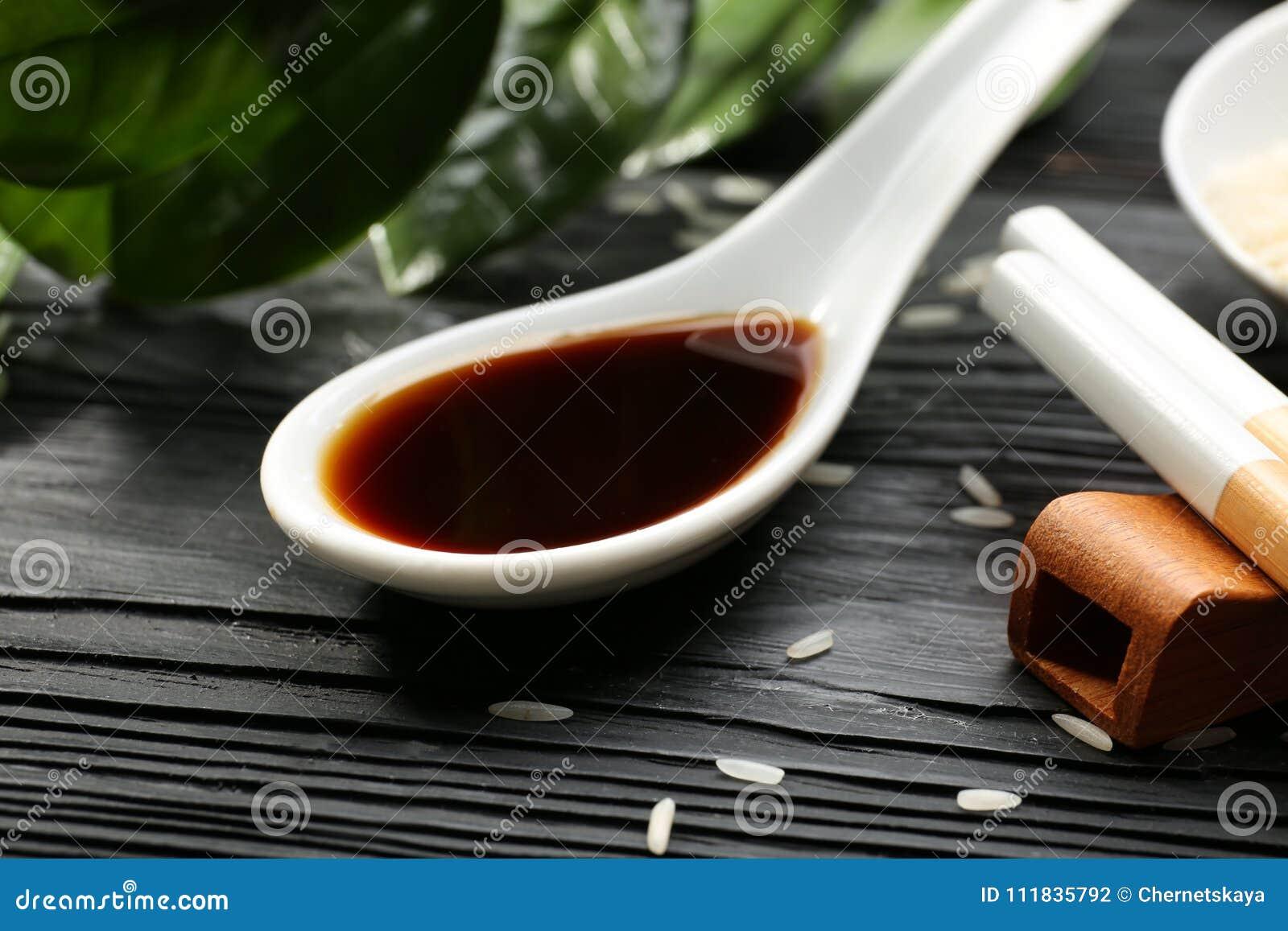 Cucchiaio con la salsa di soia saporita sulla tavola di legno,