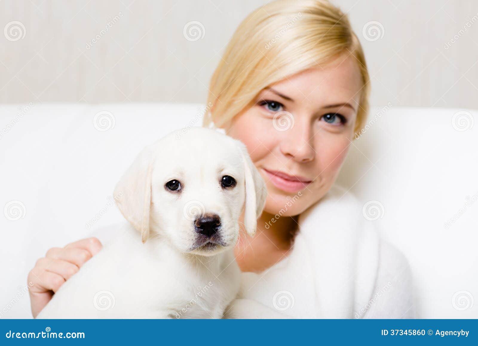 Cucciolo che si siede sulle mani della donna graziosa