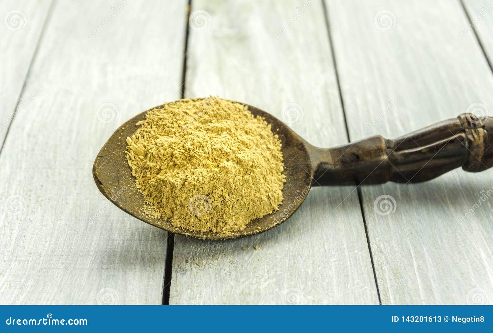 Cuchara con el polvo de la raíz de Kava Kava en el primer de madera de la tabla
