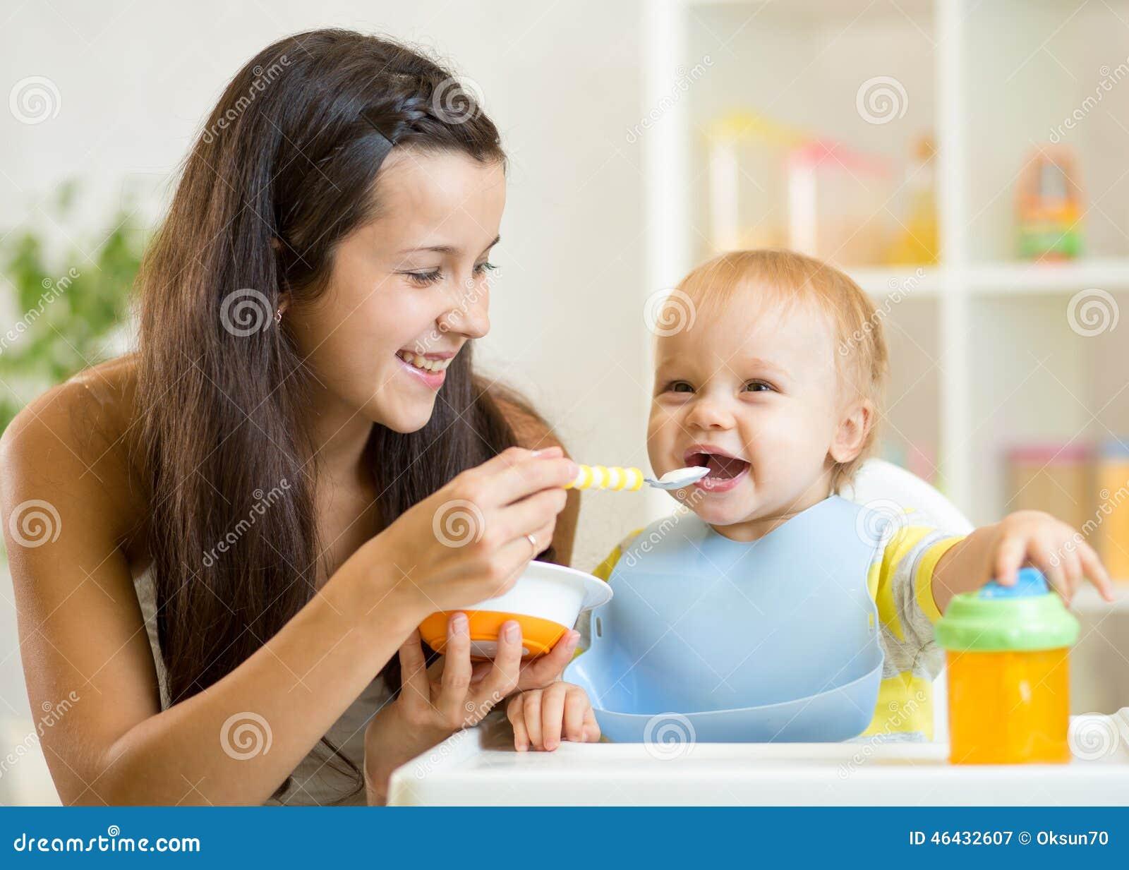Cuchara feliz de la madre que alimenta a su niño del bebé