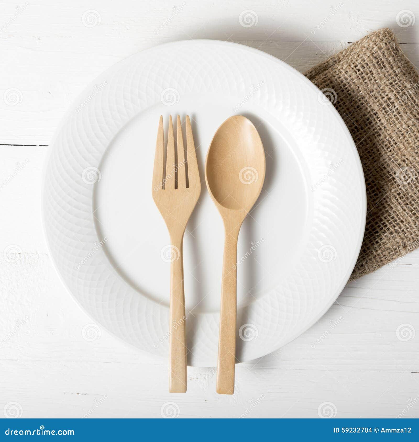 Cuchara y bifurcación de madera con el plato