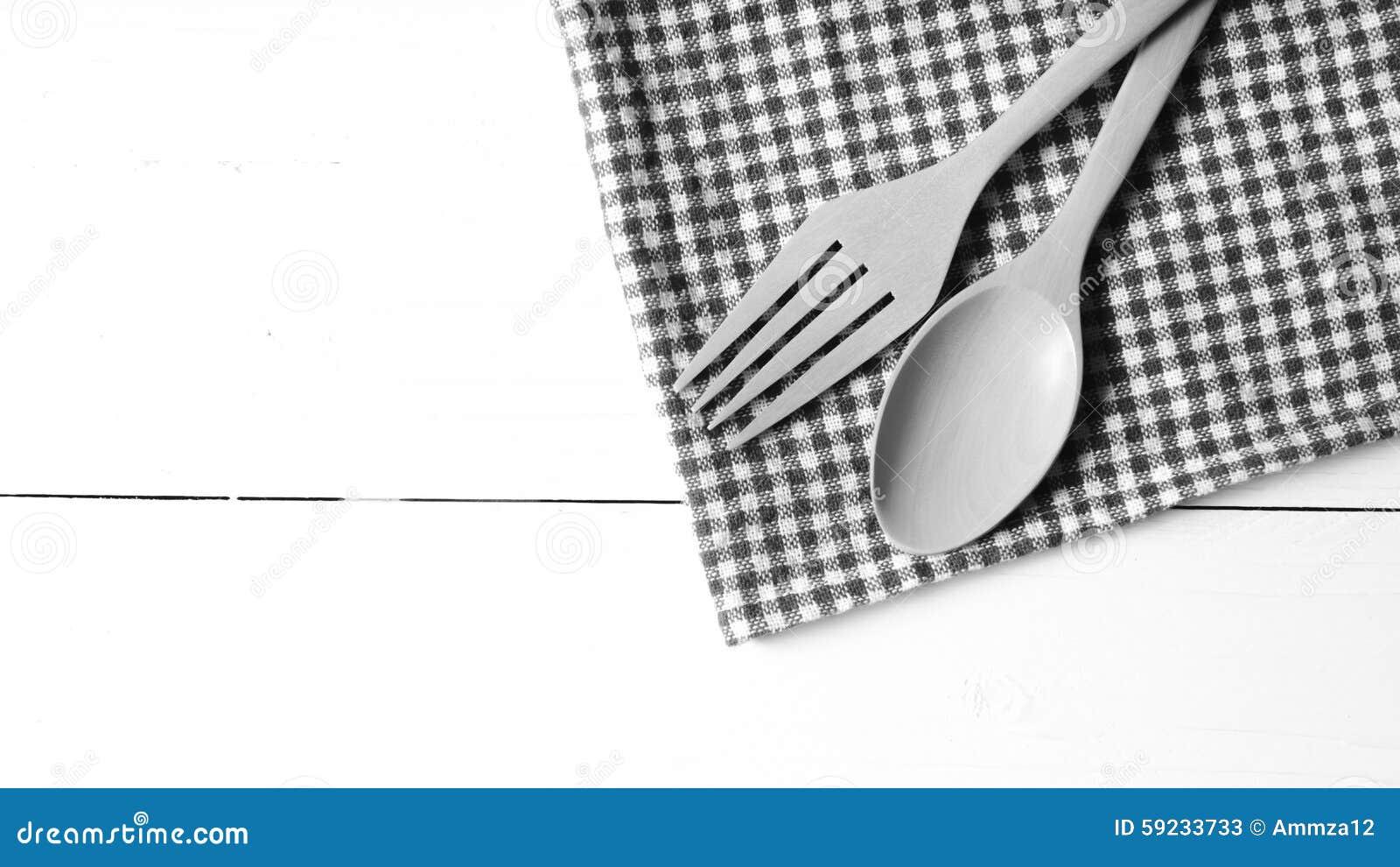 Cuchara y bifurcación de madera en color de tono blanco y negro de la toalla de cocina