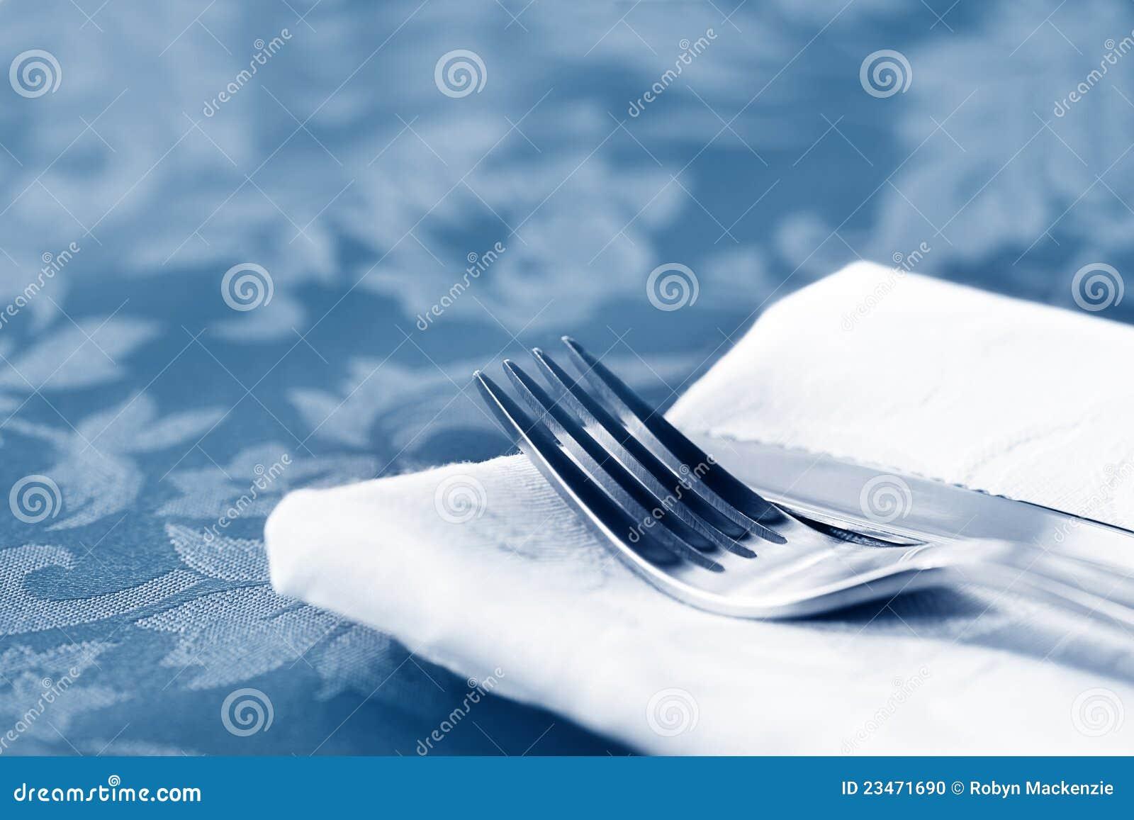 Cuchillería en el lino blanco sobre el brocado
