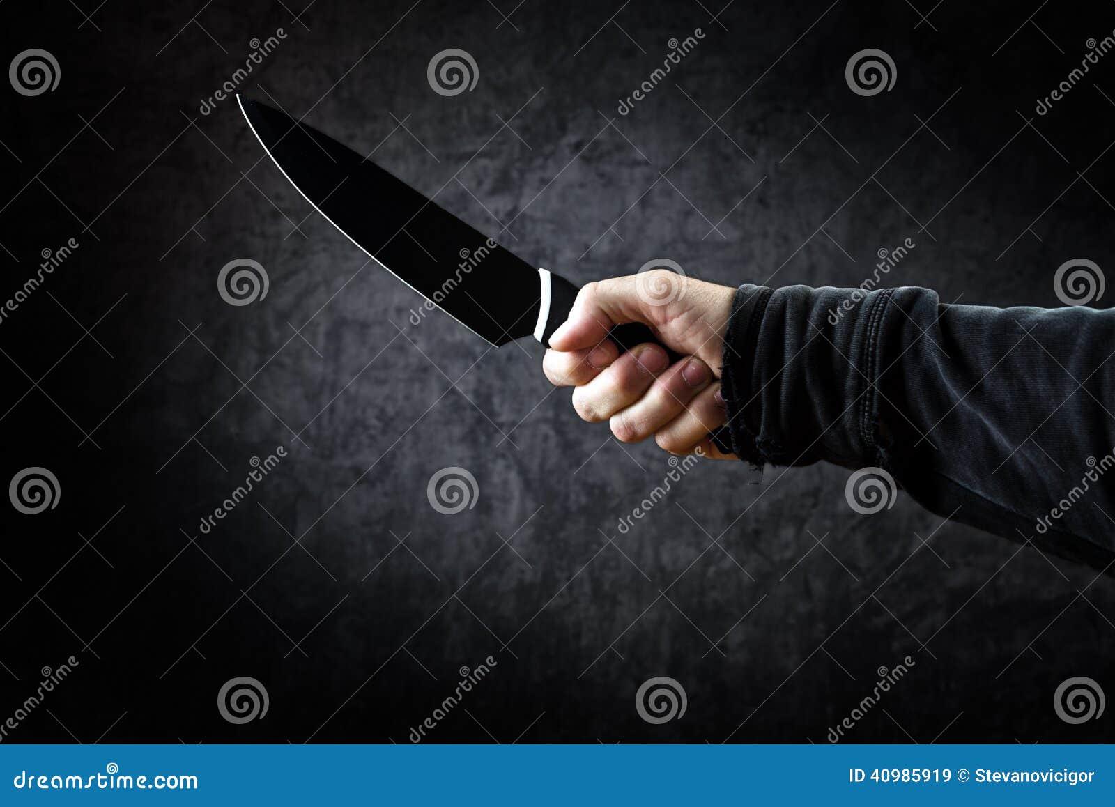 Cuchillo brillante del control malvado del hombre, asesino en la acción