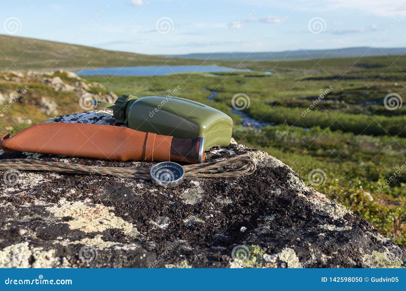 Cuchillo, compás y mapa en la roca