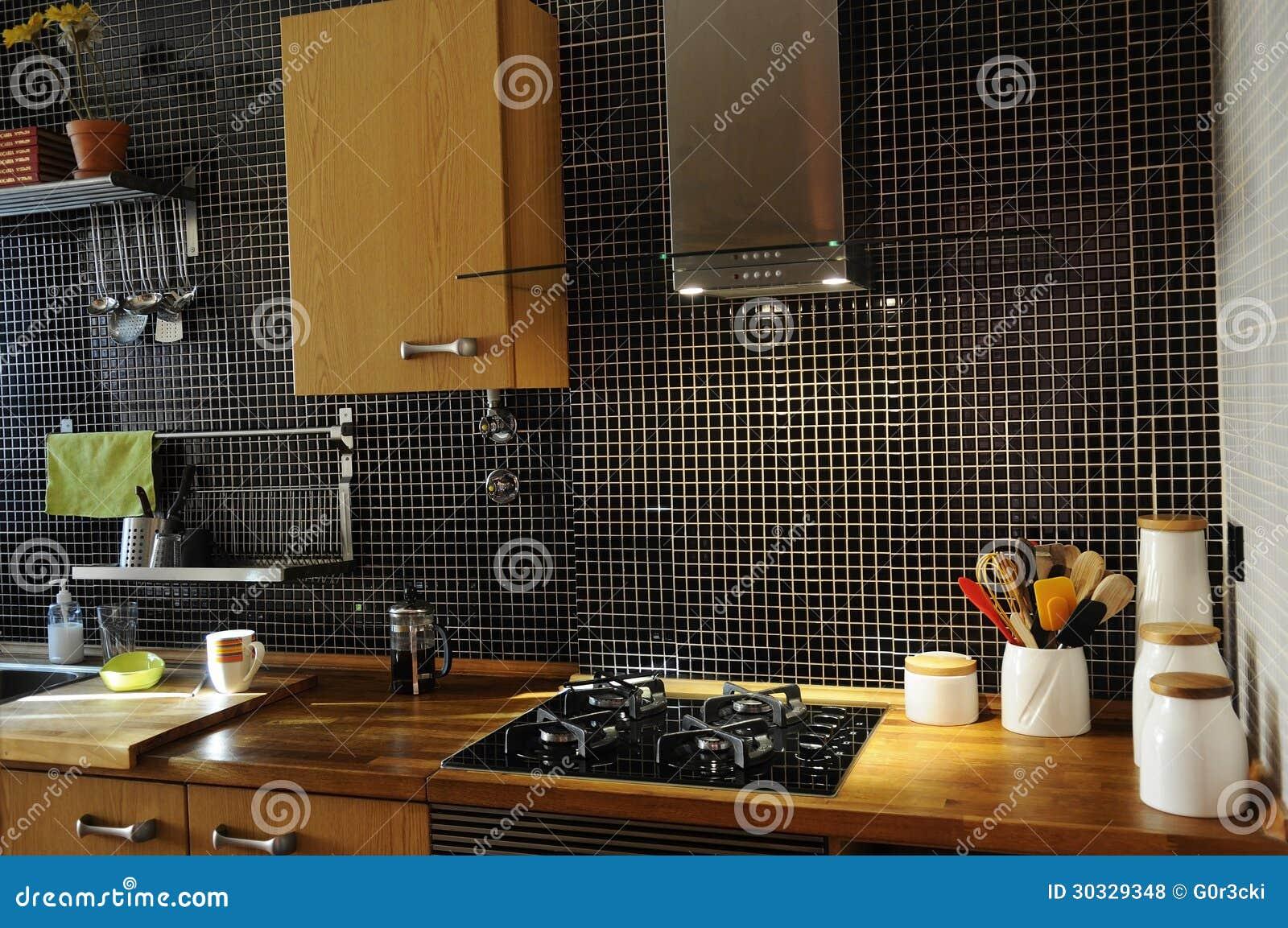 Cucina con le mattonelle nere ed il contatore di legno naturale