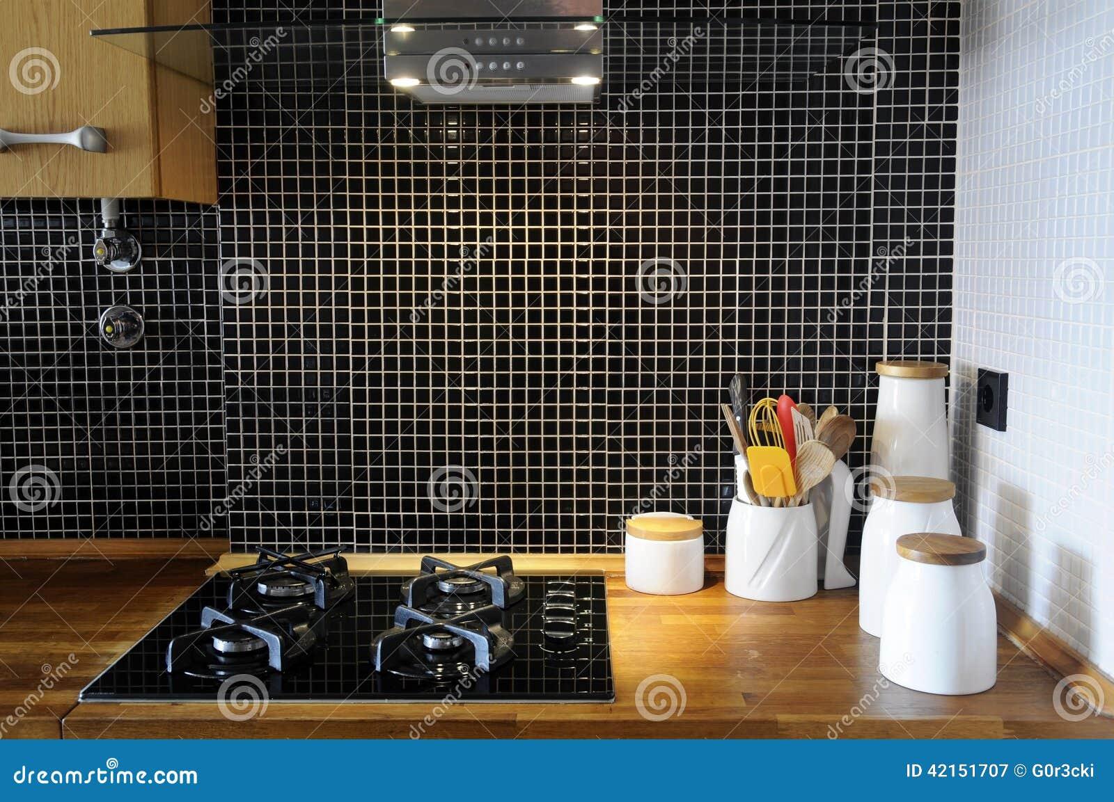 Cucina con le mattonelle nere lustrate ed il contatore di legno