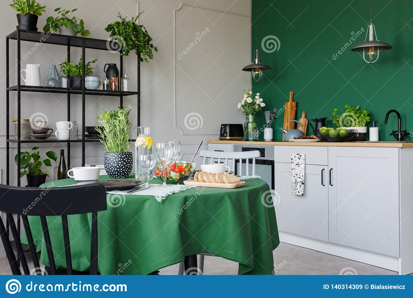 Cucina d avanguardia con il tavolo da pranzo con l insieme verde della tovaglia per la cena romantica