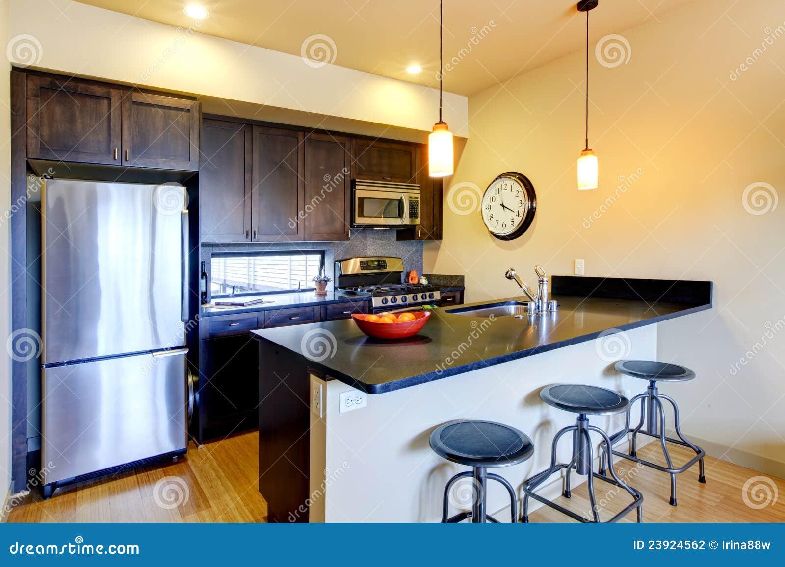 Cucina marrone moderna con la barra e gli sgabelli. fotografia stock