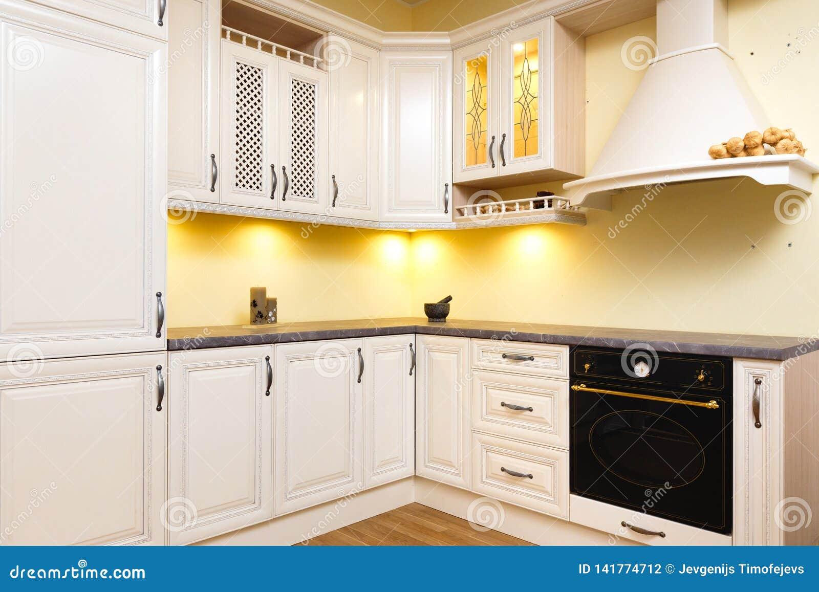 Cucina vuota bianca con mobilia bianca leggera - luci calde e legno piacevolmente decorato