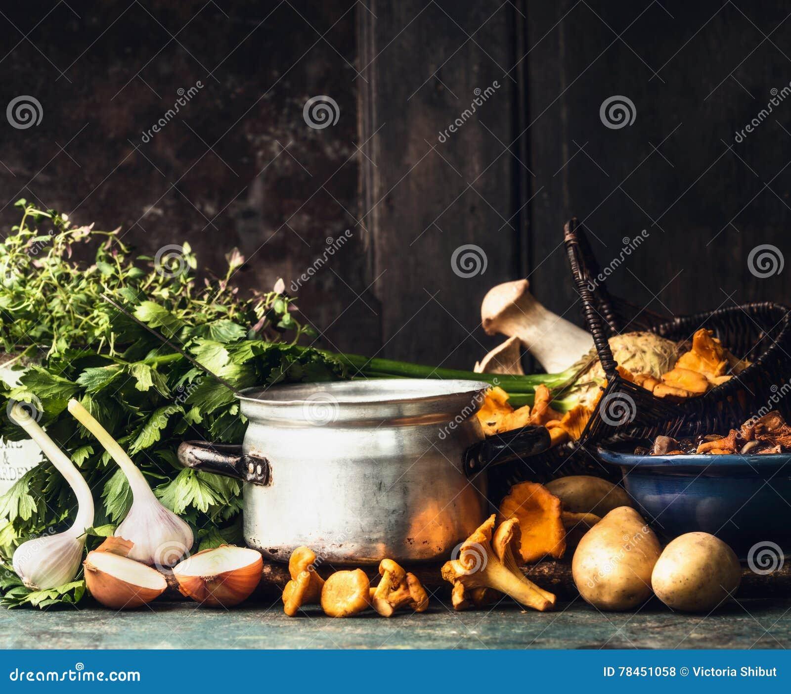 Cucinando il vaso, i funghi della foresta e cucinando gli ingredienti per minestra o lo stufato sul tavolo da cucina rustico scur